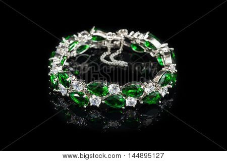 Bracelet with green stones isolated on black glass, close-up