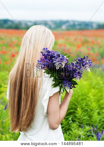 beautiful girl with bouquet of lupine flowers in hands