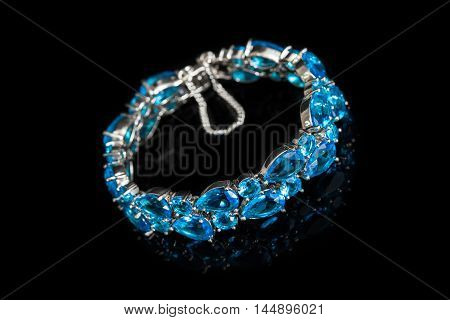 Bracelet with blue stones isolated on black glass, close-up