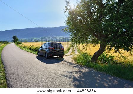PROVENCE FRANCE - JUL 17 2014: Car on the local tar road along rural field at sunset. Plateau of Sault most popular region for travel in Provence France