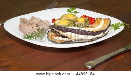 Dinner plate with meat and vegetables on wooden table