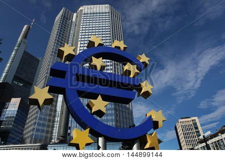 FRANKFURT AM MAIN, GERMANY - JUNE 14, 2015: Euro logo by German visual artist Ottmar Hoerl in front of the Eurotower in Frankfurt am Main, Hesse, Germany.