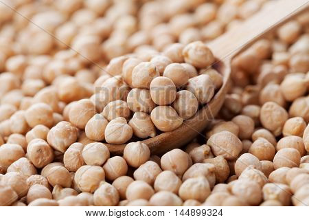 Closeup chickpea in wooden spoon and heap chickpea background.