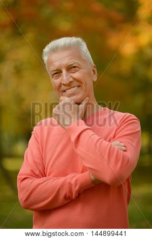 Happy elderly man enjoying in autumn park