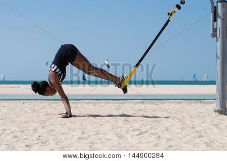 Young african woman performing difficult exercise using ropes for suspension training at Dubai beach UAE
