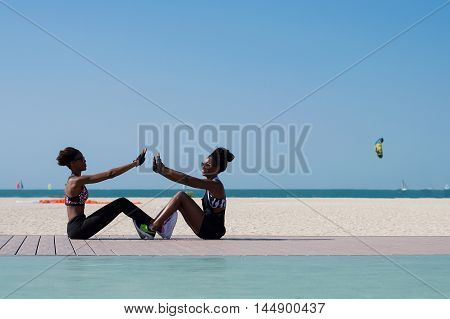 Two african girls do workout at Dubai beach in the UAE. Healthy lifestyle and outdoor activity concept