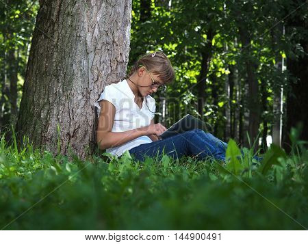 Girl teenager in sunglasses sitting alone in the park with tablet computer. Green grass summer. Dog black French bulldog
