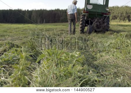 A man near a tractor seems broken outdoor shot with focus in the foreground