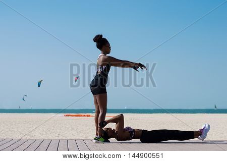 Two african females train at Dubai beach in the UAE. Two athletes in stylish sportswear and with trendy hairstyle do sport exercises in front of sandy beach and sea horizon