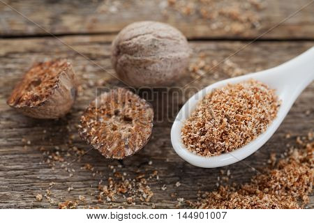 Nutmeg whole and grated on wooden background, selective focus. Macro.