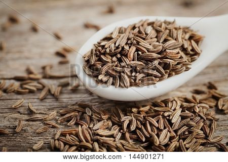 Cumin seeds or caraway in white spoon on wooden board. Macro. Organic spice.