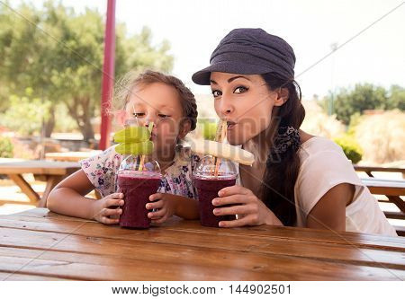 Happy Kid Girl And Funny Emotional Mother Drinking Berries Smoothie Juice Together In Street Cafe