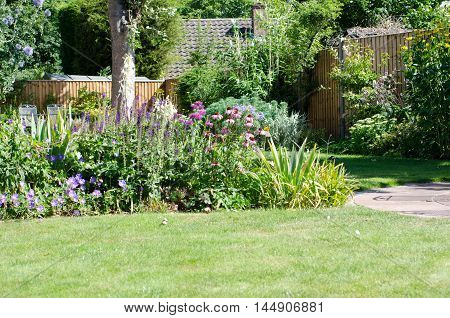 English garden on a summers day with lawn and flower beds