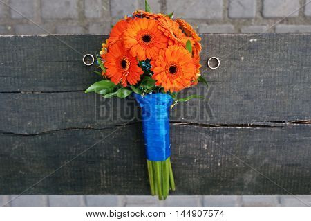 Orange Wedding Bouquet Gerbera With Rings At The Wooden Bench
