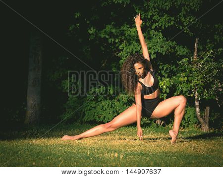 Latino dancer in black clothes dancing on grass