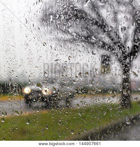 Rain on the car glass wet day shot through a windscreen focusing on the rain droplets.