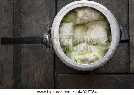 A casserole with cabbage leaves and minced meat on a wooden floor or table overhead indoor shot