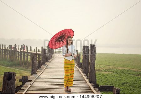 The Beautiful Burmese Woman In Myanmar Traditional Costume,with Red Umbrella Walking On Ubein Bridge