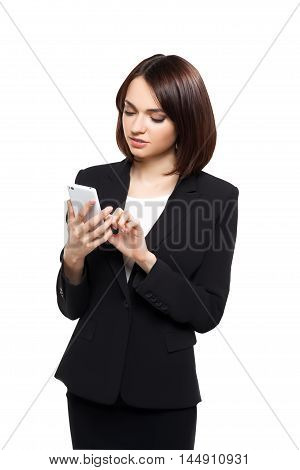 Beautiful business woman in elegant black dress typing on her smartphone isolated over white studio background.