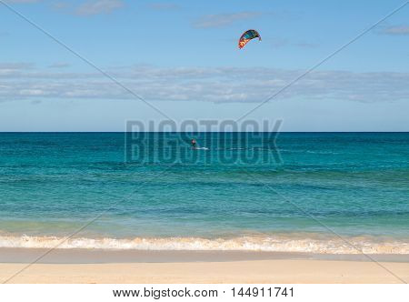 Unknown kitesurfer surfing on a flat azure water of Atlantic ocean in Corralejo Fuerteventura Canary islands Spain