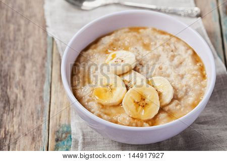 Bowl of oatmeal porridge with banana and caramel sauce on rustic table. Hot and healthy breakfast for every day. Diet and healthy food.