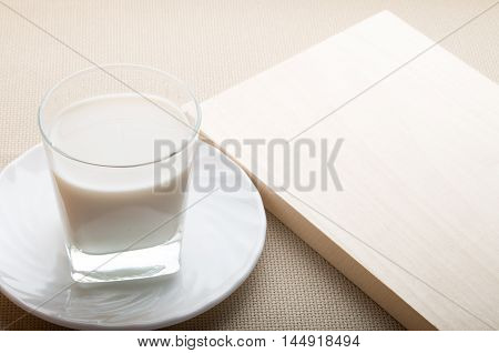 One Glass Of Milk On A White Saucer On Tablecloth Background