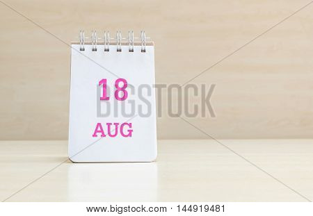 Closeup surface note book with pink 18 aug word in page on blurred brown wood desk and wood wall textured background with copy space under window light