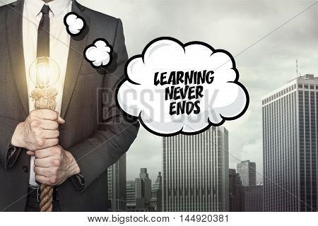 Learning never ends text on speech bubble with businessman holding lamp