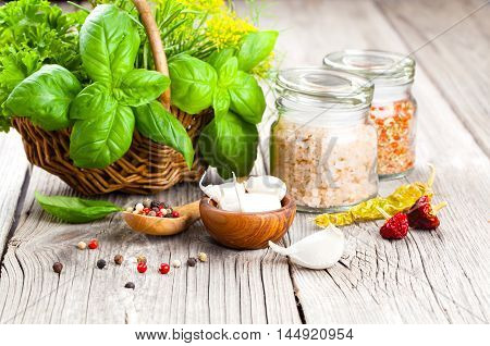 spices: garlic salt pepper and basil on a wooden background