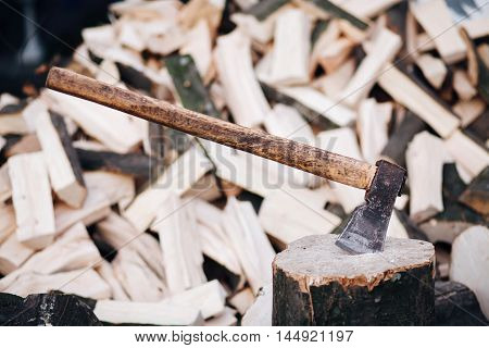 Axe stuck in a stump on a background of chopped firewood