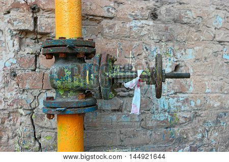 Old gas pipe painted in yellow pipe and rusty valve with spots of obsolete paint at brick wall.