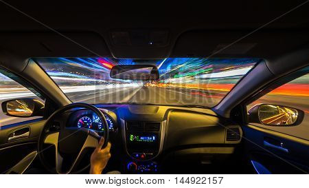 Night road view from inside car natural light street and other cars is motion blurred