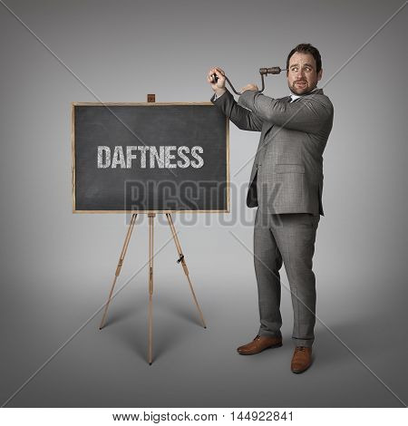 Daftness text on blackboard with businessman drilling his head