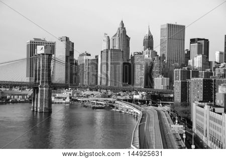 New York City skyline with Brooklyn Bridge and Lower Manhattan view in early morning sun light - Black and white toned