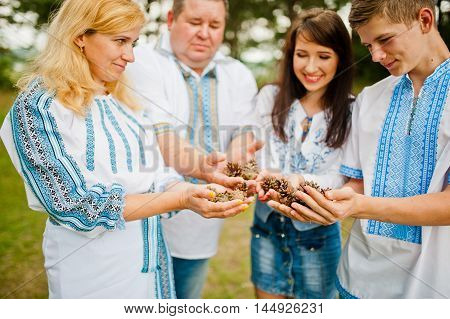 Happy Family On Pine Forest Holding Cones At Hand