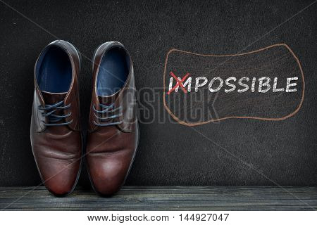 Possible text on black board and business shoes on wooden floor