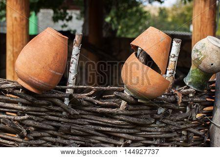 Village, rustic palisade wattle fence, old clay pots . Rural scene
