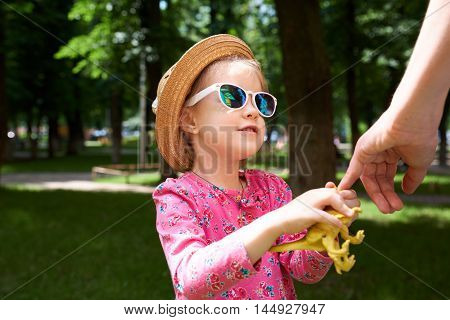 Toddler girl holding hands with her mother outside.