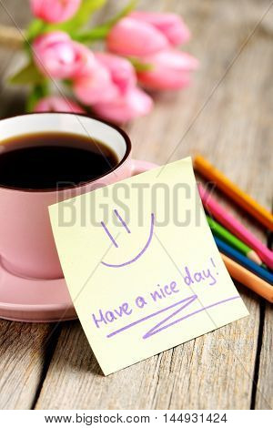 Piece of note paper on grey wooden background, have a nice day