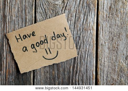 Piece of note paper on grey wooden background, have a good day