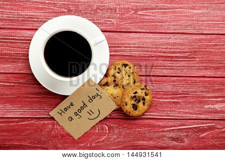 Piece of note paper with cup of coffee on red wooden background, have a good day