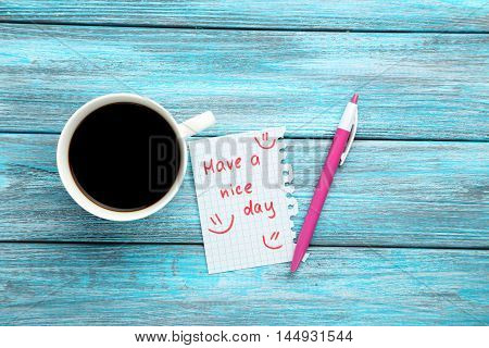 Piece of note paper on blue wooden background, have a nice day