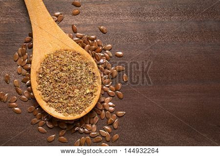 Ground or crushed brown flax seed or linseed on wooden spoon photographed on dark wood with natural light