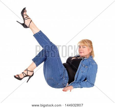 A pretty woman in jeans and jeans jacket with sitting on the floor with her legs up isolated for white background.