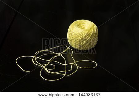 Yellow hank of woollen threads against a dark background