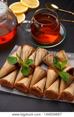 Homemade Honey Wafers Rolled Into A Cone, Filled With Condensed Milk, A Cup Of Tea And Lemon On A Bl