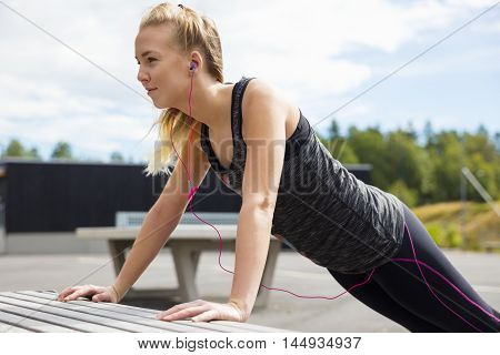 Determined young woman doing pushups on bench in park