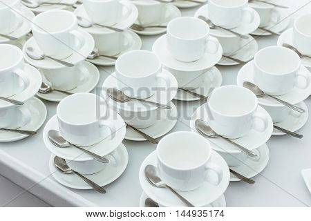 A lot of cups with white spoons on a table, for coffee or tea. Exhibited to each other.