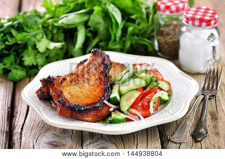 Grilled Pork chop with salad of tomatoes, cucumbers, onions, parsley and olive oil.