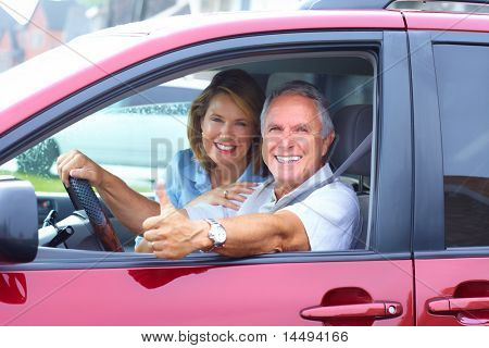 Smiling happy senior couple in the car